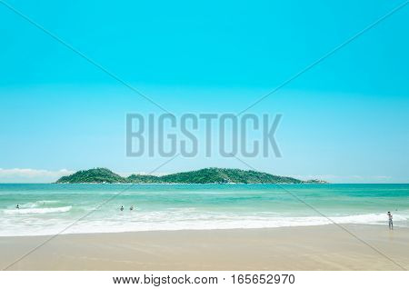 Campeche Beach: People Playing On The Beach With A Green Water And An Island On The Background On A