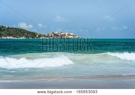 Beach And An Island In The Background On A Beautiful Sunny Day Landscape.