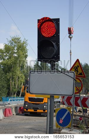 Traffic light with red light on a background of road works
