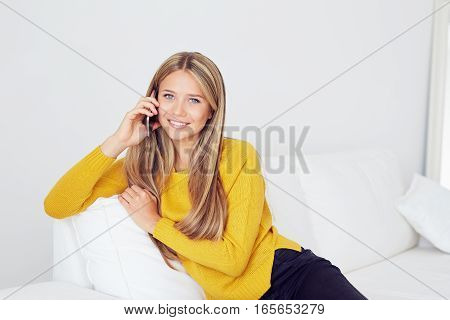 Pretty woman sitting on sofa at home and talking on mobile phone