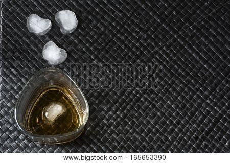 Glass of bourbon with ice on black leather background
