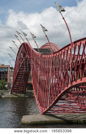 Red pedestrian bridge in Amsterdam over the river in the day with building as background