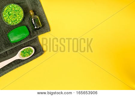 Spa set: soap, mask, oil, sea salt and towel on yellow background. Top view. Still life. Copy space