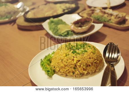 Fried rice with butter in white bowl on a wooden table.