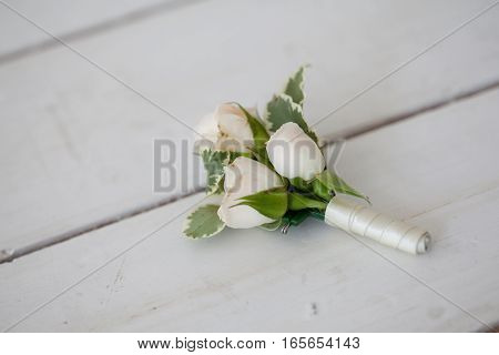 Wedding boutonniere of white roses ojn the boards