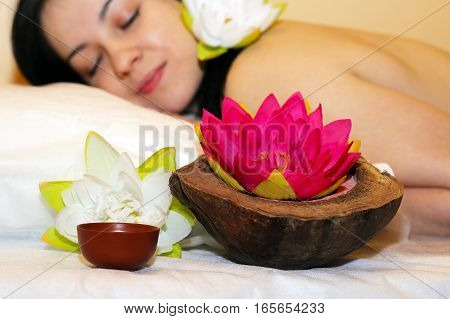 Beautiful girl ready for massage beautiful flowers