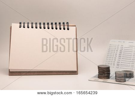 Blank notepad with calculator. Passbook blank paper and coins on white background for mocup display planning Money Financial Accounting Concept