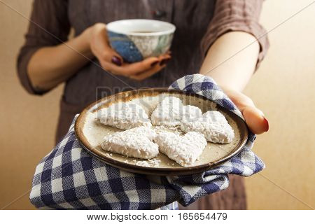 Hands holding valentine biscuit and coffee. Valentine's Day Concept