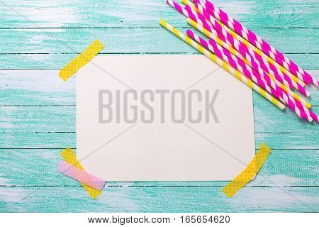 Pink and yellow paper straws and empty tag for text on turquoise wooden background. Selective focus. Place for text.