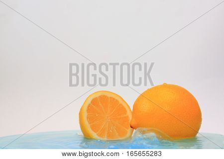 Yellow lemon in blue water with waves
