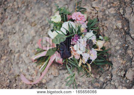 beautiful bridal bouquet of different flowers on the rocks