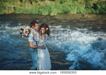 the bride and groom on the background of a mountain stream