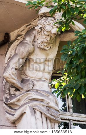 Sculpture of Atlas on the facade of the old building.