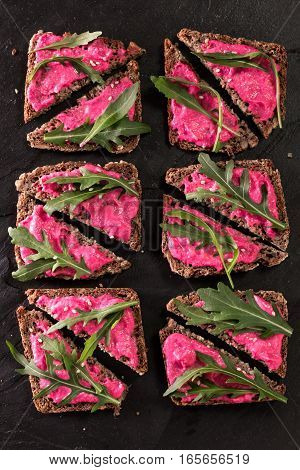 Homemade Diy Natural Vegan Very Healthy Snak With Pink Hummus And Arugula On A Wooden Table