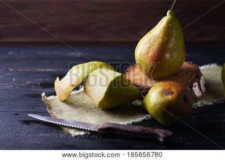 Fresh green pears and knife on a rustic background on a napkin. Vertical shot