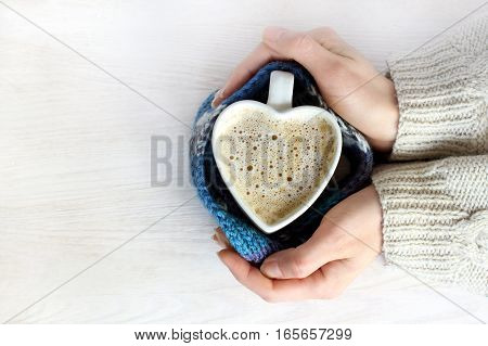 hot frothy coffee similar to a heart symbol in human hands top view / loved warming drink