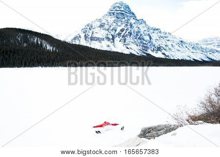 Woman Lying at Full Length on Frozen Waterfowl Lake in Winter Canadian Rockies Alberta Canada