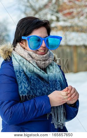 Portrait smiling brunette adult girl in big clown glasses and blue jacket with scarf outdoor standing in turn of three-quarters