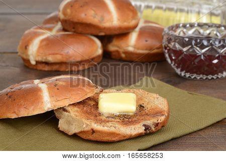 hot cross bun with butter on a green napkin
