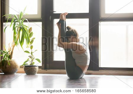 Young attractive woman practicing yoga, sitting in urdhva mukha paschimottanasana exercise, working out, wearing sportswear, grey pants, bra, indoor full length, home interior background, near window
