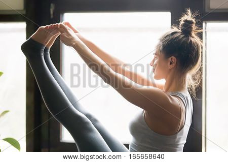 Young attractive woman practicing yoga, sitting in Both big toe exercise, Paripurna Navasana pose, working out, wearing sportswear, grey pants, bra, indoor, home interior background, close up