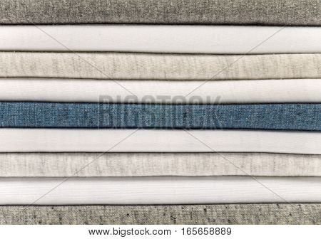Stack of white gray and heather blue t-shirts