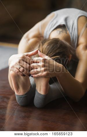 Close up of young woman practicing yoga, sitting in Seated forward bend exercise, paschimottanasana pose, working out, wearing sportswear, grey pants, bra, indoor, home interior background, vertical