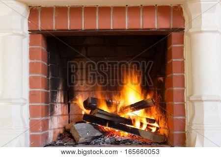 Warm cozy burning fire in a brick fireplace close up. Cozy background.