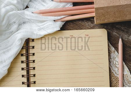 Blank notebook with lace and pencils on wooden background