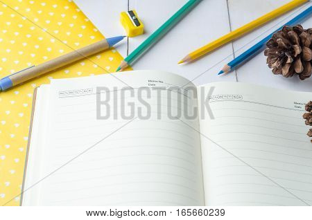 Blank daily planner notebook with pen and color pencils on white wooden background
