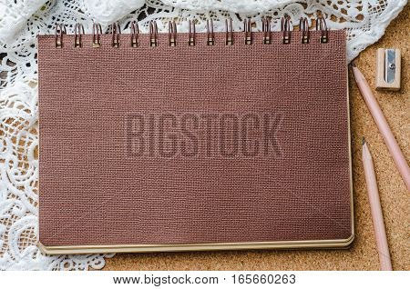 Brown paper diary with pencils and pencil sharpener on wooden background