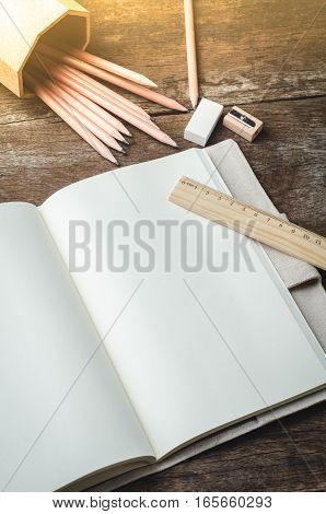 Blank daily planner notebook with pencils pencil sharpener ruler and eraser on wooden background