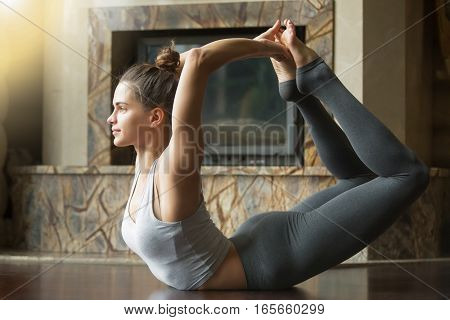 Young happy smiling attractive woman practicing yoga, stretching in Bow exercise, Dhanurasana pose, working out, wearing sportswear, indoor full length, home interior background, near fireplace