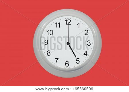 Wall watch showing five o'clock isolated on red background