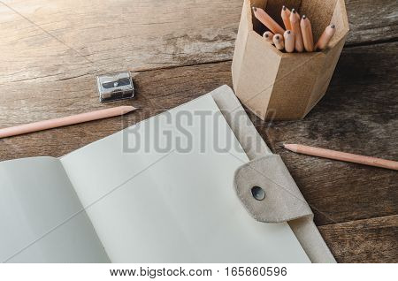 Blank daily planner notebook with pencils and pencil sharpener on wooden background