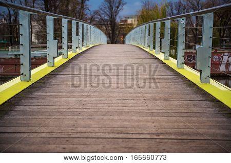 Wooden bridge over a river. Bridge in the city