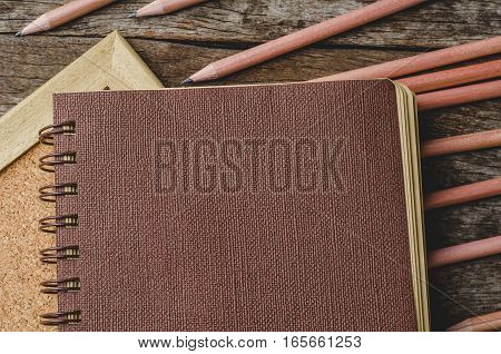 Brown paper diary with pencils on corkboard and wooden background