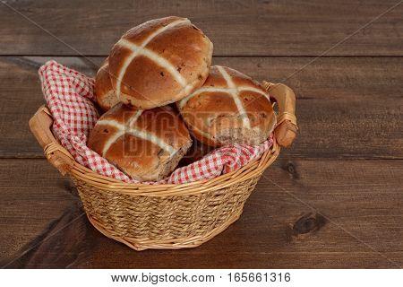 wicker basket of hot cross buns on a wood table