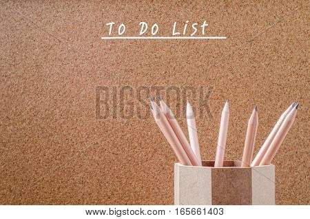 Empty to do list with pencils in wooden holder on brown background