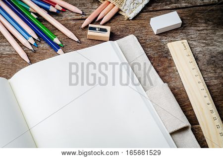 Blank daily notebook with color pencils pencil sharpener ruler and eraser on wooden background