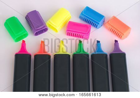 Six black color markers with open caps closeup
