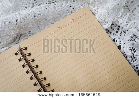 Blank notebook with lace on wooden background