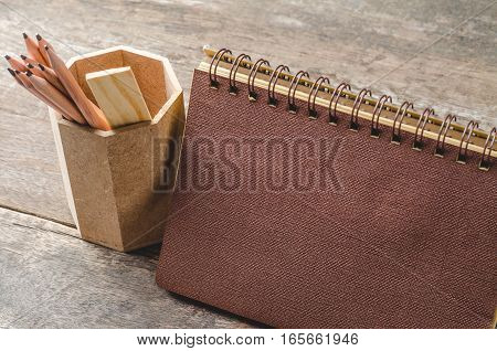 Brown paper diary with pencils in holder on wooden background