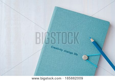 Blue notebook with color pencil on white wooden background