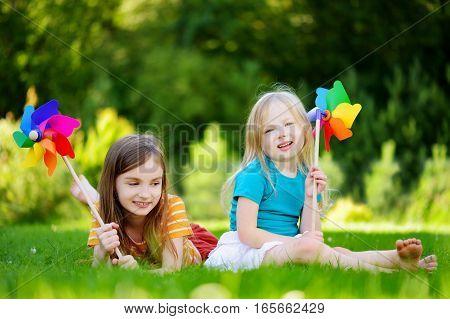 Two Cute Little Girls Holding Colorful Toy Pinwheels On Sunny Summer Day