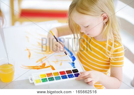 Cute Little Girl Drawing With Colorful Paints At A Daycare