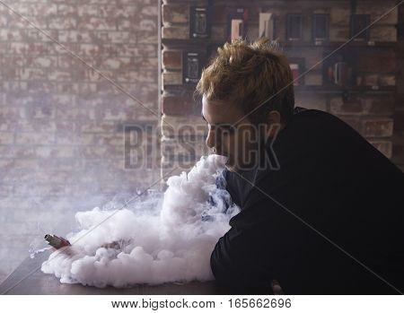 The man smoke an electronic cigarette at the vape shop
