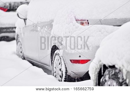 Snow covered cars are seen during snowfall in the city