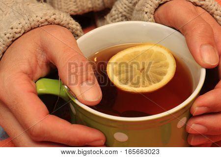 Green mug with polka dots hot tea with lemon and hands