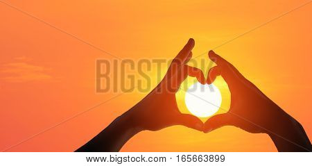 Panorama silhouette of female hands making a heart shaped symbol with beautiful sunset background.